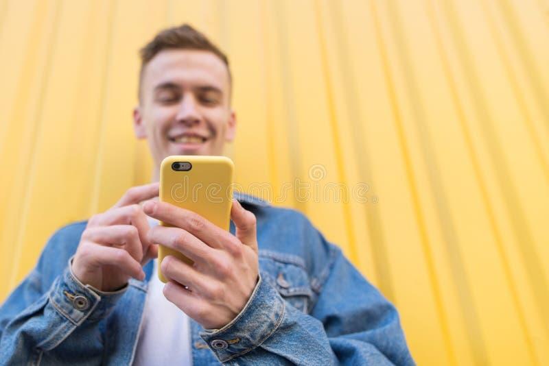 młody człowiek cieszy się smartphone w jaskrawej pokrywie na żółtym tle obrazy royalty free