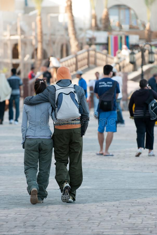 Młody człowiek i dziewczyna obejmujemy wzdłuż nabrzeżne deptaka gdy cieszą się wakacje przy nadmorski obraz royalty free