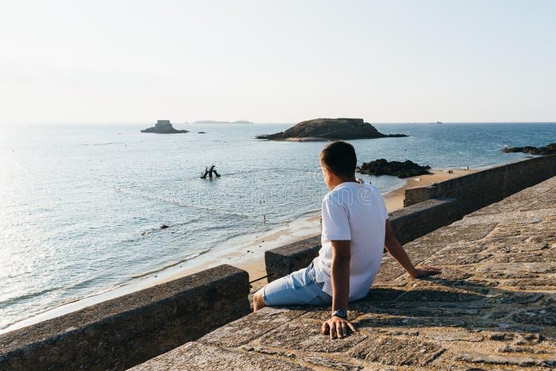 Młody człowiek ogląda zmierzch w zatoce Saint Malo fotografia royalty free