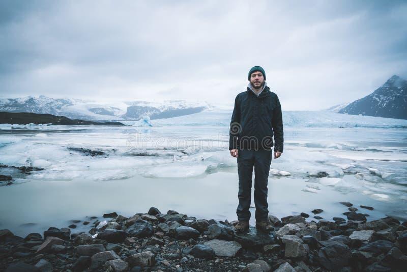 Młody człowiek pozycja przed Fjallsarlon góry lodowej laguną przy południową końcówką lodowiec Vatnajokull z unosić się, obrazy stock