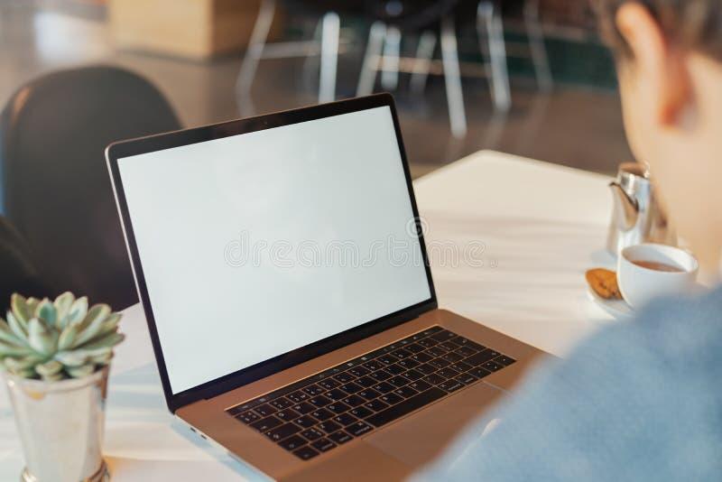 Młody człowiek pracuje przed laptopem z pustym bielu ekranem zdjęcia royalty free