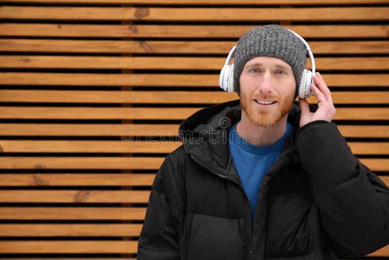 Młody człowiek słucha muzyka z hełmofonami przeciw drewnianej ścianie obrazy royalty free