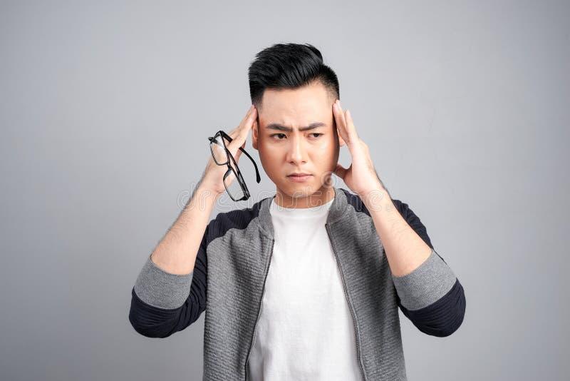 Młody człowiek trzyma jego głowę patrzeje puszków spojrzenia z palcami w oba rękach męczył z migreną, odizolowywającą na szarym t fotografia stock