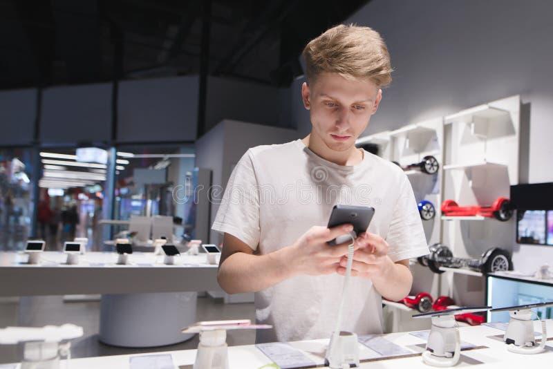 młody człowiek używa telefon w elektronika sklepie Wybór smartphone w elektronika sklepie obrazy royalty free