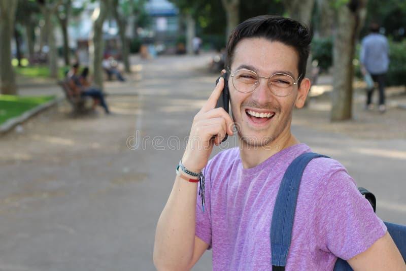 Młody facet śmia się za głośnym podczas rozmowy telefoniczej obrazy royalty free