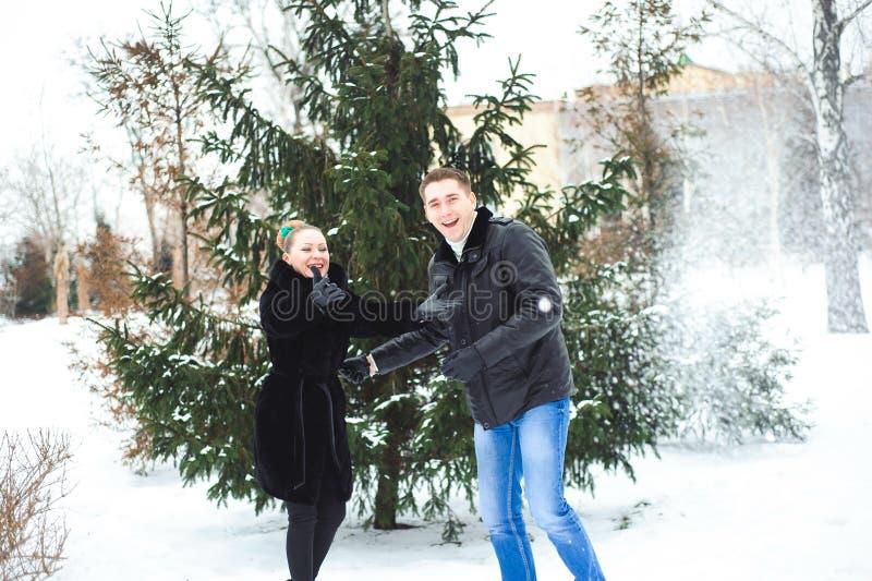 Młody facet i dziewczyna w winterwear cieszy się opad śniegu obrazy royalty free