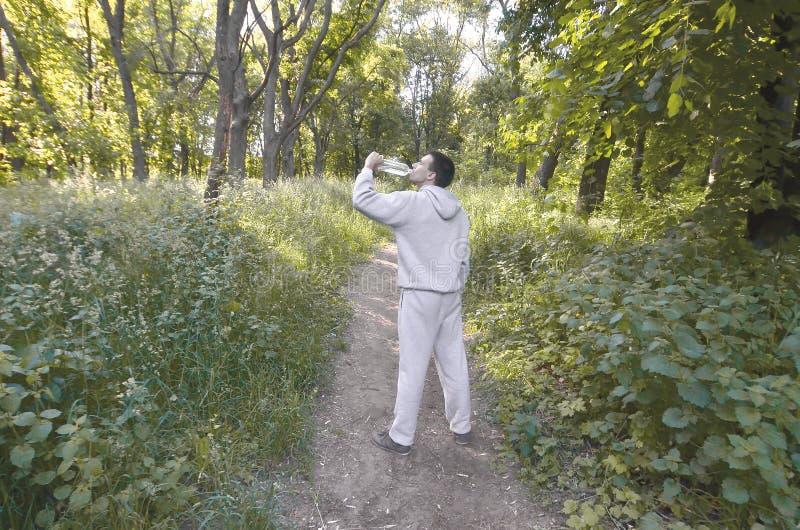 Młody facet w szarości bawi się kostiumów napojów wodę od butelki amo fotografia stock