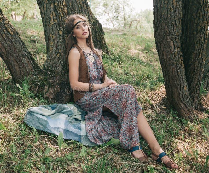 Młody hipis kobiety obsiadanie blisko drzewa w lesie obraz stock