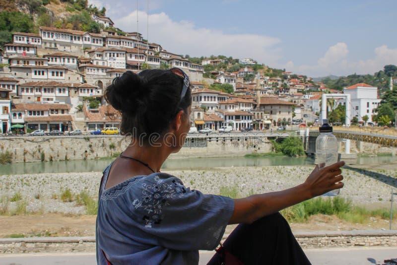 Młody Kaukaski dziewczyna podróżnik siedzi z ona z powrotem spojrzenia przy Albańskim miastem Berat i kamera fotografia royalty free