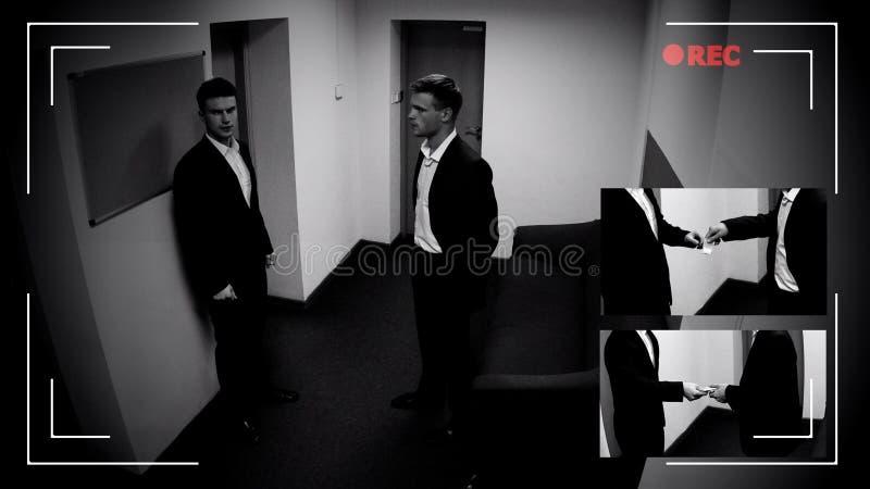 Młody kierownik daje narkotykom współpracownik, CCTV kamery dowód, przestępstwo rejestr zdjęcia royalty free