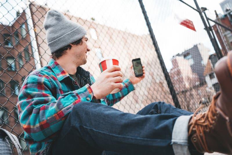 Młody modny mężczyzny obsiadanie na ulicznym chodniczku odpoczywa z filiżanką gorąca kawa i używa smartphone dla wideo połączenia zdjęcia royalty free