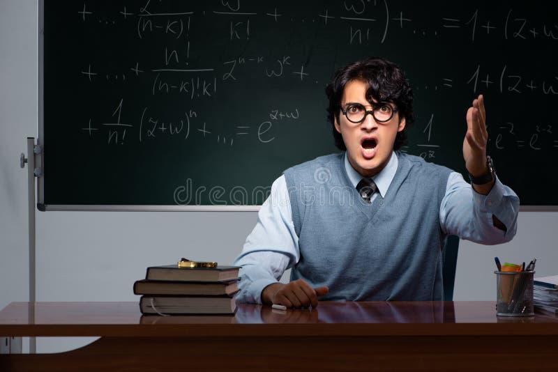 Młody nauczyciel matematyki przed chalkboard zdjęcia royalty free