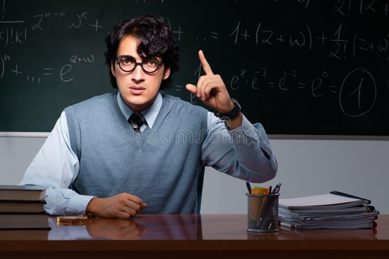 Młody nauczyciel matematyki przed chalkboard zdjęcia stock