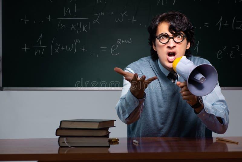 Młody nauczyciel matematyki przed chalkboard fotografia royalty free