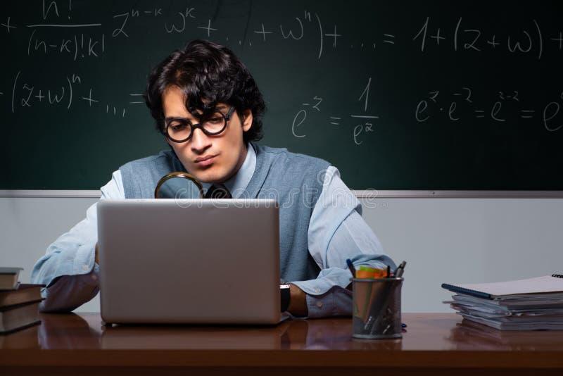 Młody nauczyciel matematyki przed chalkboard zdjęcie stock
