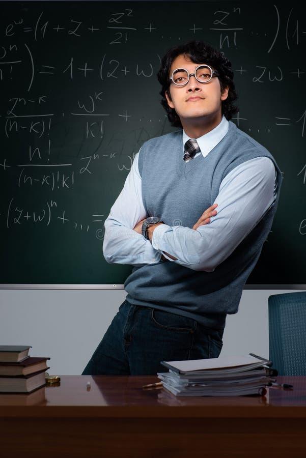 Młody nauczyciel matematyki przed chalkboard obrazy stock