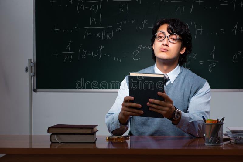 Młody nauczyciel matematyki przed chalkboard zdjęcie royalty free