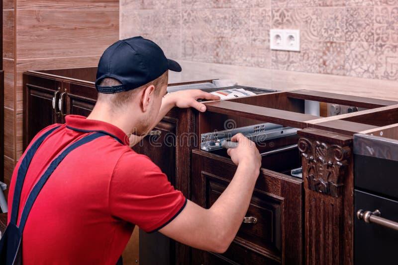 Młody pracownik instaluje kreślarza Instalacja nowożytny drewniany kuchenny meble zdjęcia stock