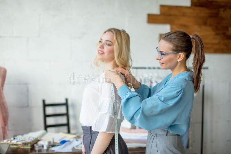 Młody projektant mody bierze pomiary kobieta projekt nowa suknia fotografia royalty free