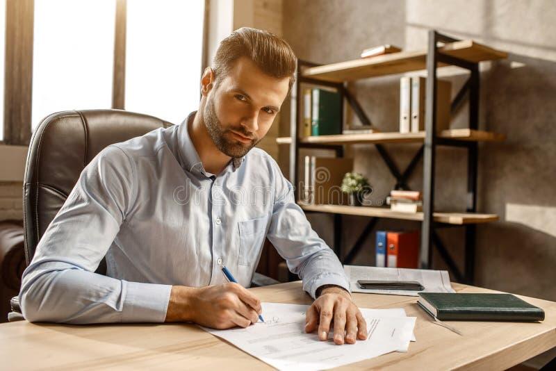 Młody przystojny biznesmen pisze w jego swój biurze siedzi przy stołową reklamą Stawia podpis na doucments i patrzeje na kamerze zdjęcia stock