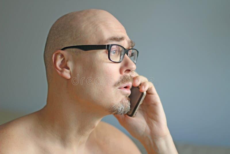 Młody przystojny mężczyzna w czarnych szkłach opowiada na telefonie Duzi problemy, skandal, zła wiadomość zbliżenie odizolowywają fotografia stock
