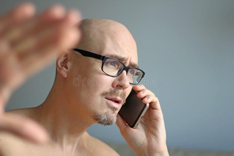 Młody przystojny mężczyzna w czarnych szkłach opowiada na telefonie Duzi problemy, skandal, zła wiadomość zbliżenie odizolowywają zdjęcie stock