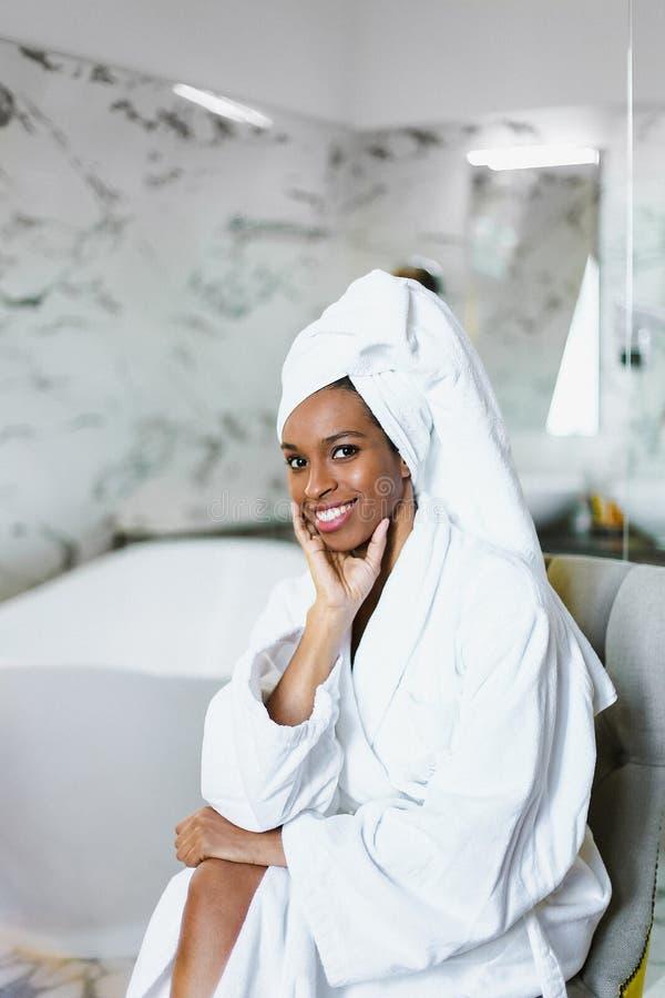 Młody uśmiechnięty afro amerykański dziewczyny obsiadanie w łazience i być ubranym białego bathrobe fotografia royalty free
