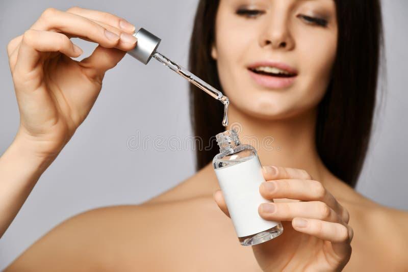 Młodych kobiet krople kryształ - jasny kosmetyk od pipety w szklanym słoju i przewidują przyjemność brać opiekę ona obraz royalty free