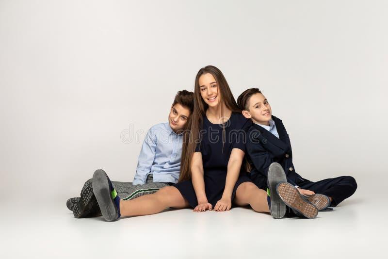 Młodzi piękni nastolatkowie siedzi wpólnie na ziemi zdjęcia royalty free
