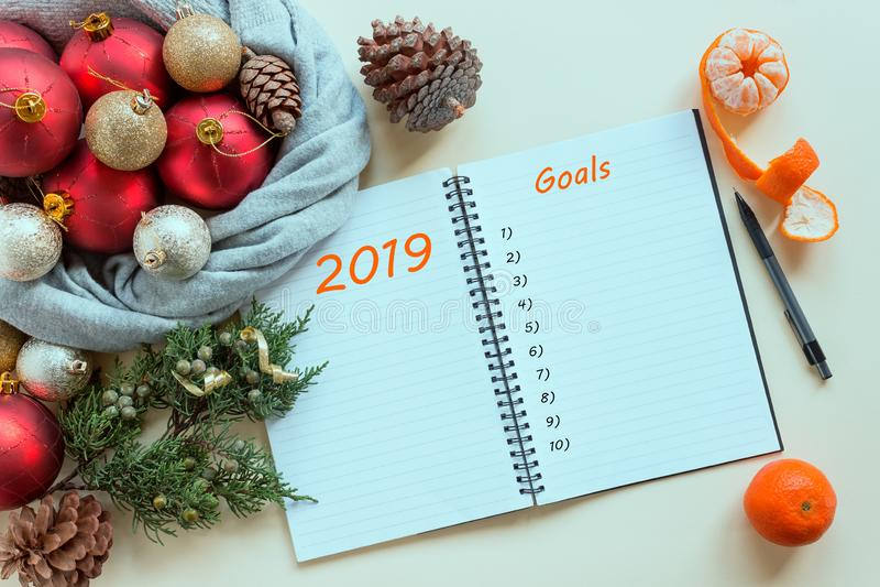 2019 mål Att att göra listan i notepad bredvid julpynt, kottar och tangerin royaltyfria bilder
