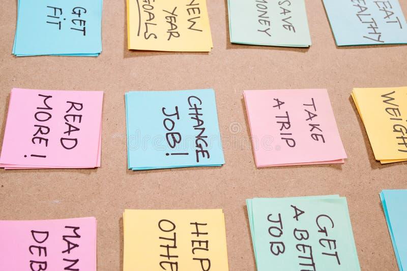 Mål för nytt år eller upplösningar - färgrika klibbiga anmärkningar på en Notepad med kaffekoppen royaltyfria bilder