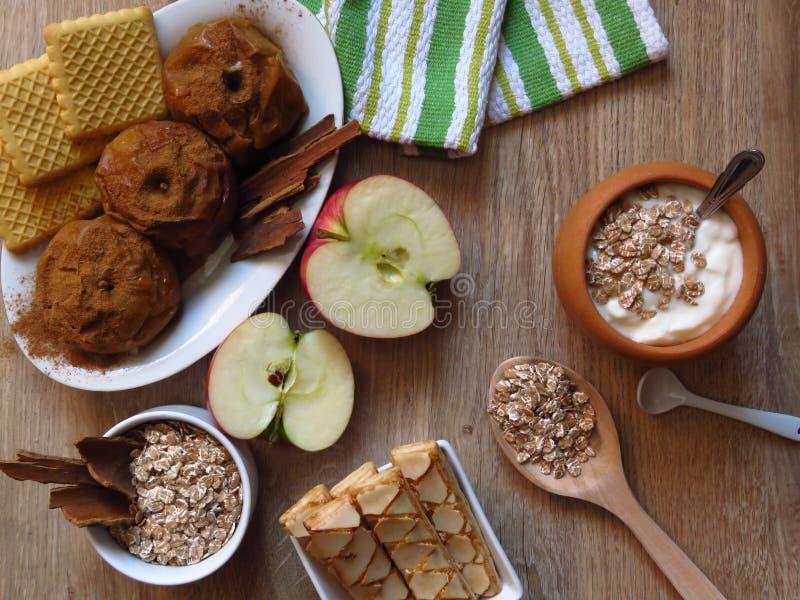 Mål för sädes- korn för havre som bakas och fressäpplen, kex, yoghurt och kanel på lantlig bakgrund för stilekträ arkivbild