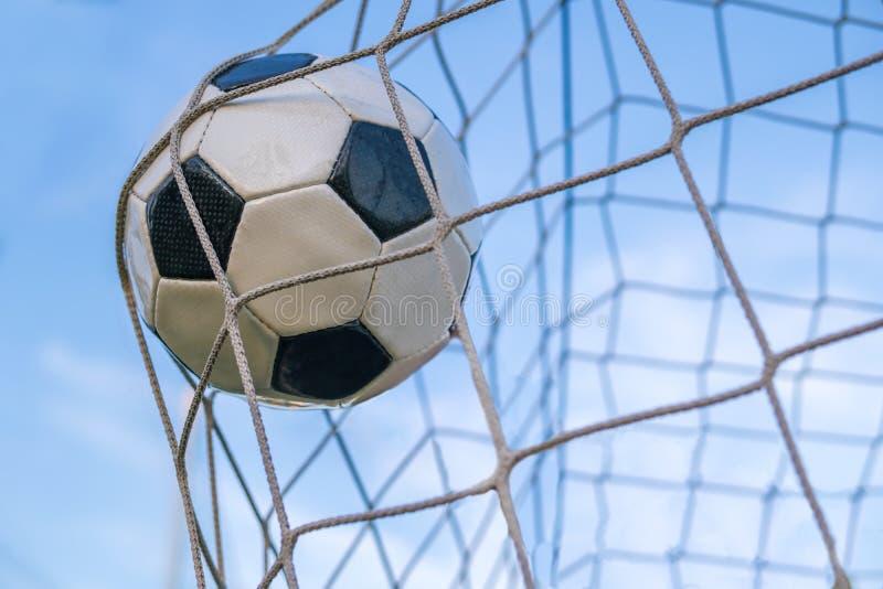 Mål - fotboll- eller fotbollboll i det netto mot blå himmel royaltyfri foto