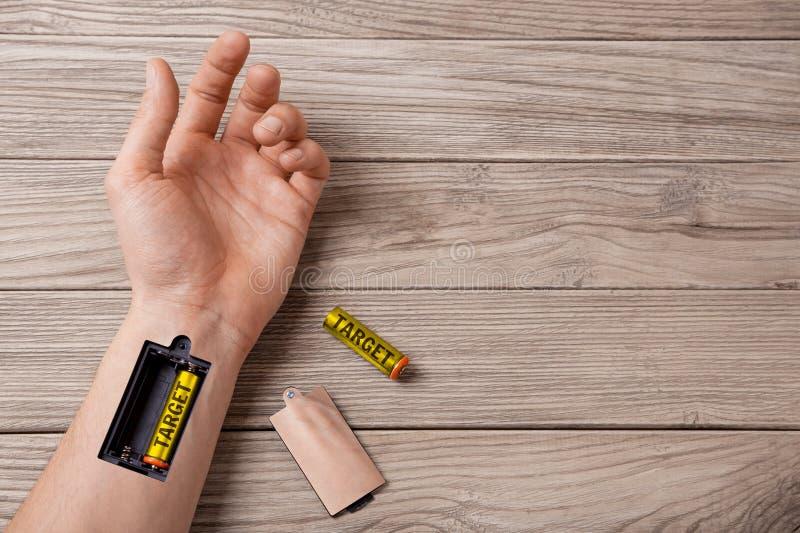 Mål Hand av en man med springan för laddande batterimål royaltyfri bild