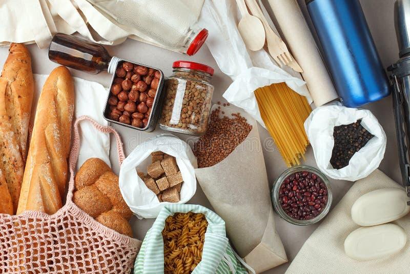 Mål i ecobomullspåsar, exponeringsglas och papper som förpackar på tabellen i köket från marknad Nollförlorat shoppingbegrepp för royaltyfria foton