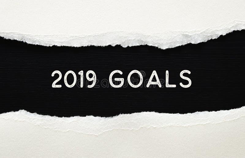 2019 mål listar skriftligt över sönderrivet papper på svart bakgrund royaltyfri bild