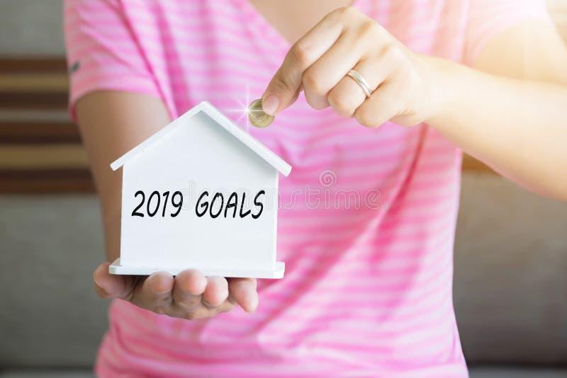 2019 mål med kvinnahanden som sätter pengarmyntet i spargrisen, Sav royaltyfria foton