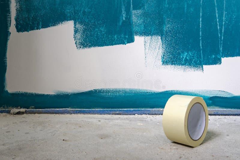 Måla arbeten på en vägg Med en rulle av kanalbandet i förgrunden Pågående arbete arkivfoton