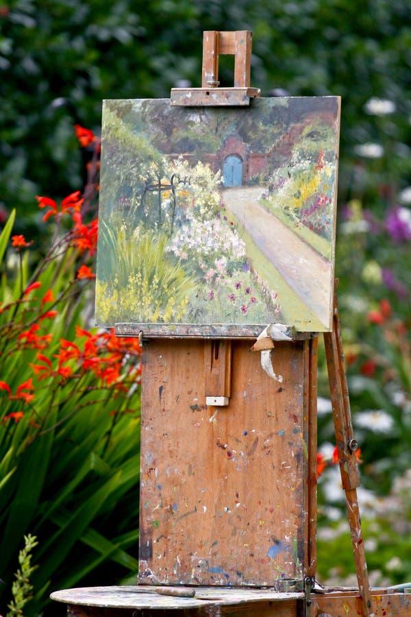 Måla av en oljabild i en trädgård arkivfoto
