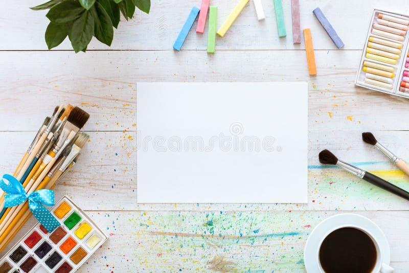 Måla borstar, paintboxen med vattenfärger, färgpennor, kaffe och tom åtlöje upp papper på vit träbakgrund, konstnärlig bakgrund, fotografering för bildbyråer