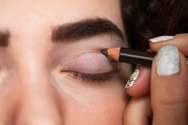 Måla en tjock linje på ditt klippta veck med hjälpen av en kosmetisk blyertspenna royaltyfri bild
