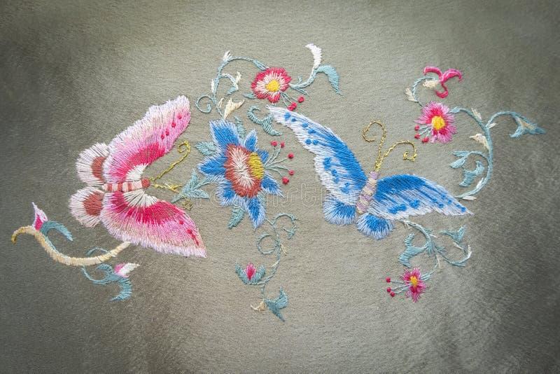 Måla fjärilar och handgjord blommabroderi royaltyfria foton