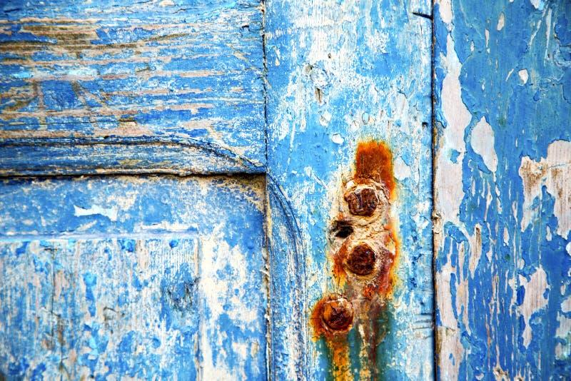 Måla i den rostiga blåa wood dörren spikar fotografering för bildbyråer