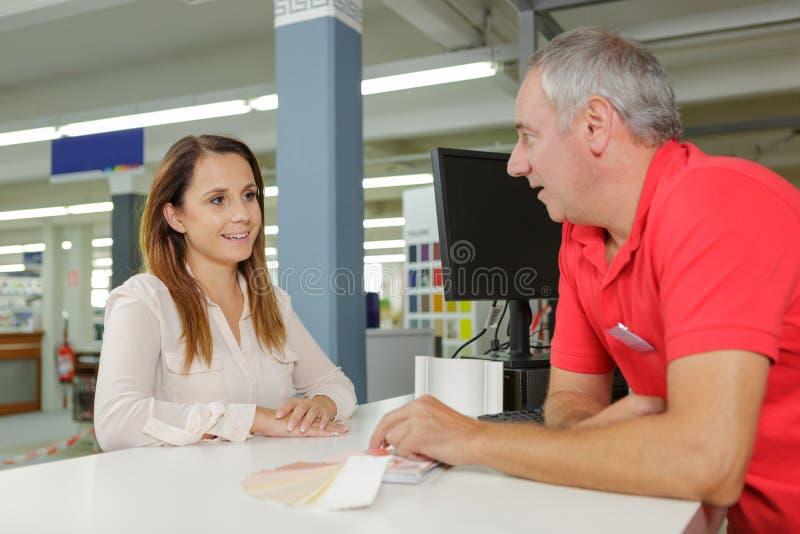 Måla lagerarbetaren som talar till kunden över räknare arkivfoton