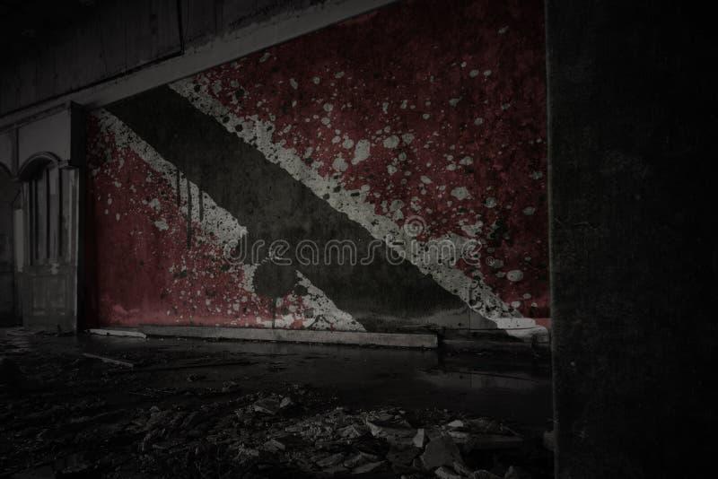 M?lad flagga av Trinidad och Tobago p? den smutsiga gamla v?ggen i ett ?vergett f?rst?rt hus royaltyfri fotografi