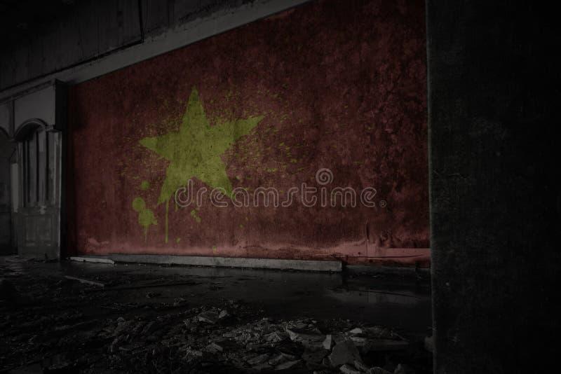 Målad flagga av Vietnam på den smutsiga gamla väggen i ett övergett förstört hus royaltyfri bild