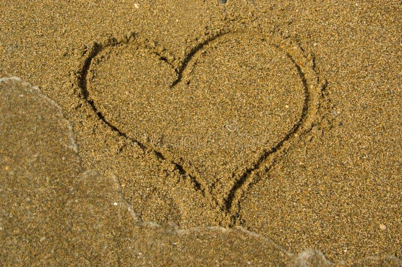 Målad hjärta på sanden nära havet arkivfoto