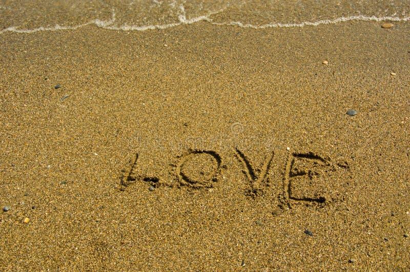 Målad hjärta på sanden nära havet arkivfoton
