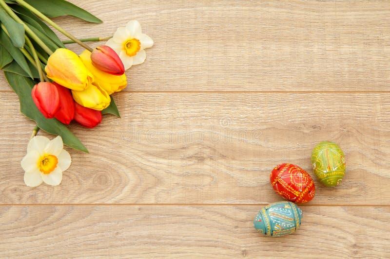 Målad påskägg, tulpan och pingstlilja på träbräden arkivfoton