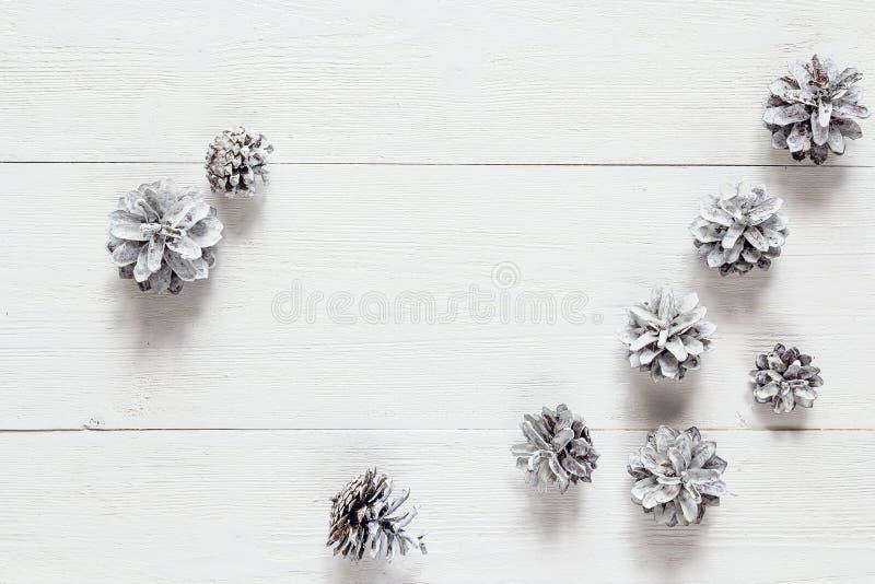 Målad snö sörjer kottar på den lantliga vita wood tabellen Utrymme för te royaltyfri foto